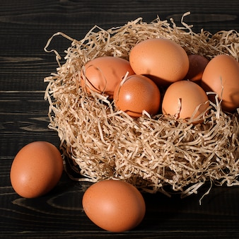 素朴な木製、黒、暗い背景に巣に新鮮な茶色の卵。