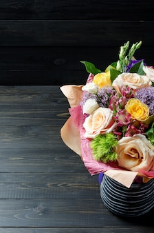 Букет цветов на темном деревянном фоне. букет с розами.
