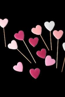 分離された黒地にハートの形の棒にピンクと白のクッキー。バレンタイン・デー。