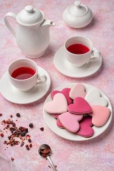 ベリーティーとアイシングでハート形のクッキー。コンセプト:バレンタインティーパーティー、ピンクのお祝いテーブルの設定。