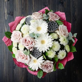 Букет цветов на темном деревянном фоне. букет из роз.