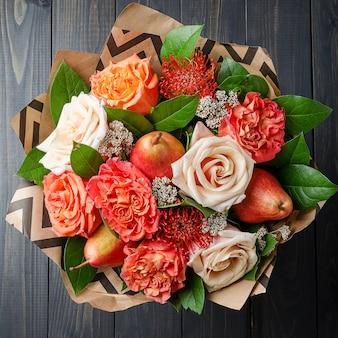 Букет цветов с грушами на темном деревянном фоне. фруктовый букет.