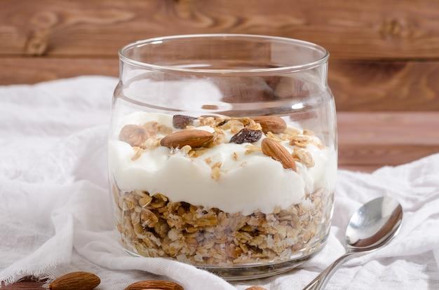 Мюсли с натуральным йогуртом, орехами и сухофруктами в стеклянной банке