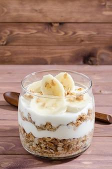 Мюсли с натуральным йогуртом, бананом, орехами и сухофруктами в стеклянной банке