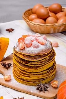 Стек самодельных тыквенных панкексов с сахарной пудрой на вершине и засахаренным кумкватом.