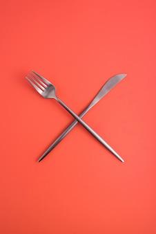 交差したフォークとオレンジ色の背景、ケータリング、カフェ、レストランのシンボルにナイフ。