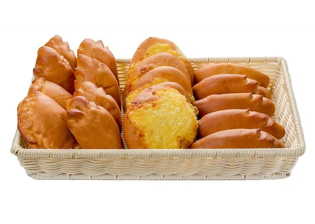 孤立した白地にさまざまな品種のバスケットのパンの品揃え。