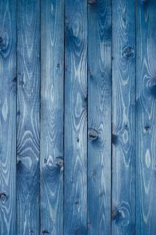 濃い青で塗られた、狭い板で作られた濃い青の木製の背景。