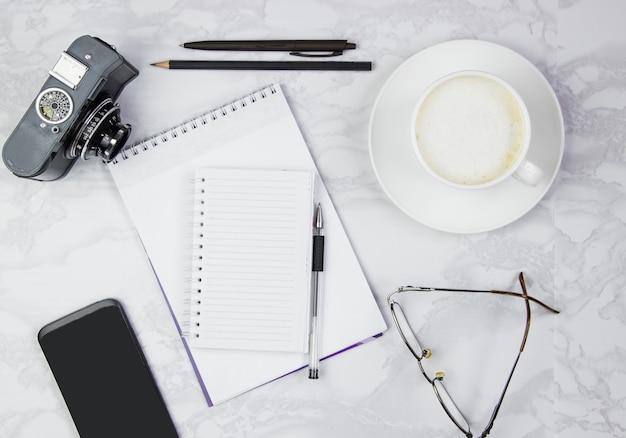 Рабочее место с блокнотом, телефоном, ручкой, очками, камерой и чашкой кофе на мраморном столе. вид сверху, плоская планировка, копирование пространства