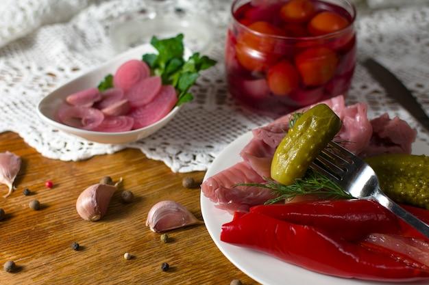 さまざまな種類の漬物。キュウリのピクルス、トマト、キャベツ、コショウ、緑、タマネギ、ニンニクを古いスタイルのテーブルで提供