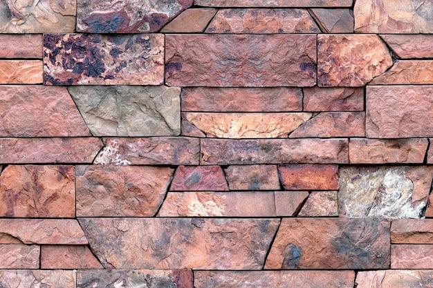 Бесшовный фон из декоративной гранитной плитки. картина каменной стены для внешней и внутренней отделки. красный гранитный камень