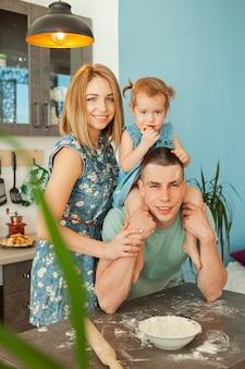 食料を準備する台所で幸せな笑みを浮かべて白人家族