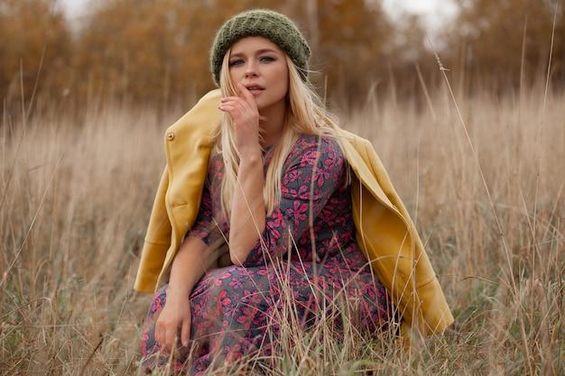 緑の帽子と黄色のコート、スモーキーアイメイク、乾いた草で毛を飛んでセクシーな美しい女性の肖像画