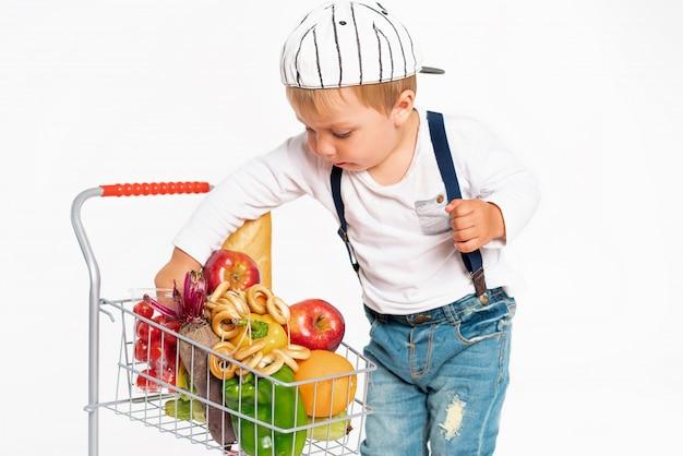 健康食品バスケットとスタジオに立っているカジュアルな服で陽気な男の子。ショッピング、割引、販売のコンセプト