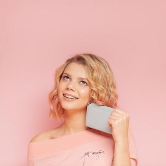 色の毛とピンクの背景にパスポートを保持しているタトゥーの若い学生女性