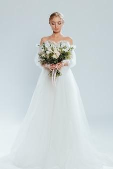 花束のバラとウェディングドレスでポーズをとって若い美しい花嫁