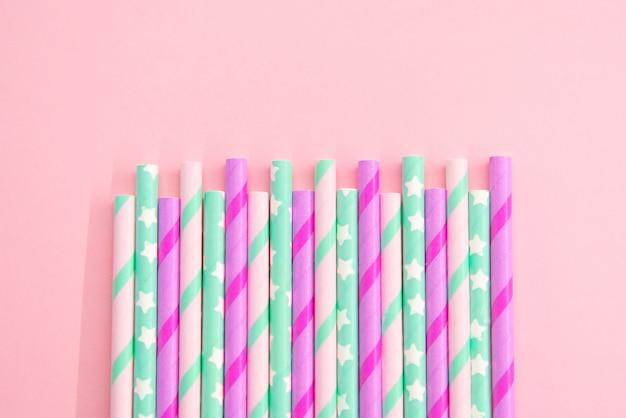 Красочные бумажные коктейльные трубки на розовом фоне. эко дружественных. ноль отходов