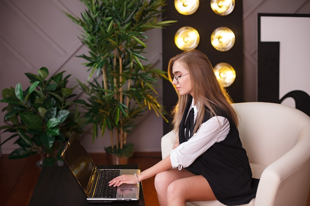 Красота молодой женщины в очках, размещения в офисе с ноутбуком.
