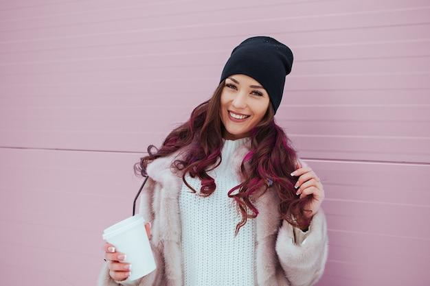 ミンクのコートと黒い帽子でコーヒーを飲みながら美容ファッション笑顔の女性の肖像画。アウトドア