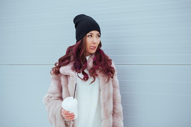 ミンクのコートと黒い帽子で舌を示すコーヒーと美容ファッション笑顔の女性の肖像画。コピースペース