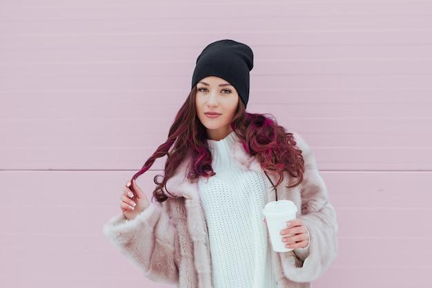 ミンクのコートと黒い帽子でコーヒーを飲みながら美容ファッション笑顔の女性の肖像画。コピースペース。着色された毛。