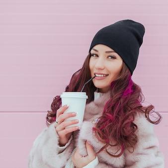 ミンクのコートと黒い帽子で舌を示すコーヒーと美容ファッション笑顔の女性の肖像画。コピースペース。色付きの髪