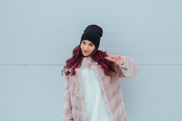 ミンクのコートで指で平和を作る色オンブル髪型と美容ファッション笑顔の女性の肖像画