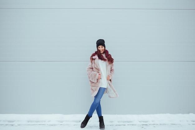 カラフルなピンクの壁にスマートフォンでミンクのコートでかなり笑顔の女性のファッションの肖像画。