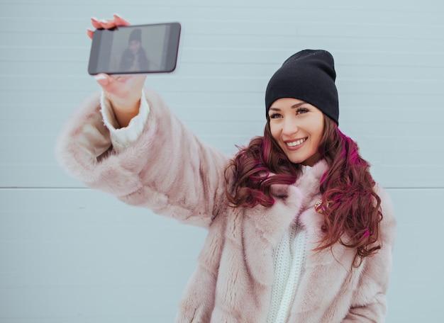 ミンクのコートとカラフルな灰色の壁にスマートフォンでかなり笑顔の流行に敏感な女性のファッションの肖像画。自撮りを作成しています。カジュアルな服装。色付きの髪