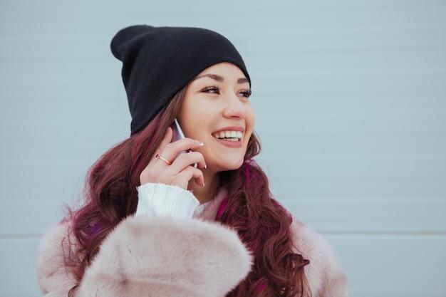 ミンクのコートとカラフルな灰色の壁にスマートフォンでかなり笑顔の流行に敏感な女性のファッションの肖像画。話す。カジュアルな服装。色付きの髪