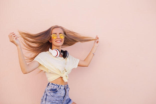 Портрет красоты моды улыбающихся молодых женщин с желтыми очками, наушниками