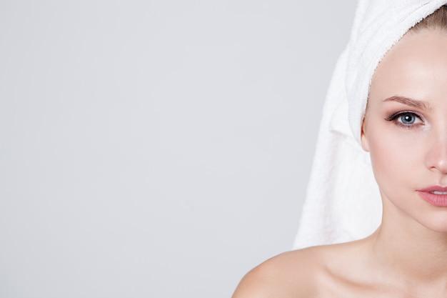 カメラを見て彼女の頭にタオルを持つ若い女性。屋内。スキンケア