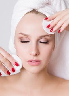 彼女の頭にタオルを持つ若い女性。綿パッドで化粧を削除