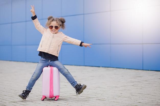 Маленькая мода курчавая усмехаясь девушка в солнечных очках сидя на чемодане и показывая мир пальцами.