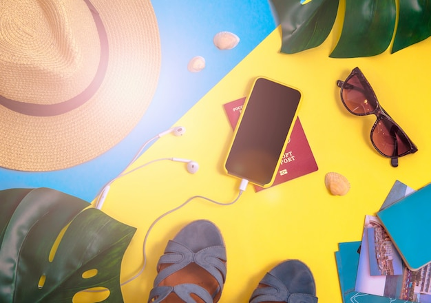 モンステラ葉、スマートフォン、ヘッドホン、わら帽子、その他のアクセサリーが付いているフラットレイ