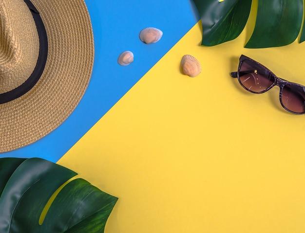 モンステラの葉、わらの帽子、その他のアクセサリーのフラットレイ