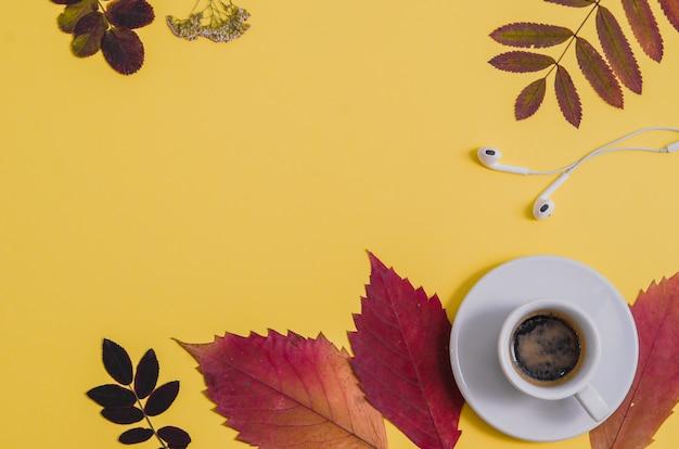 黄色の背景に植物園とヘッドホンを備えたコーヒー。秋。
