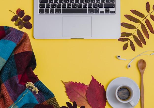 黄色の背景にコーヒー、植物園、毛布のあるノートパソコン