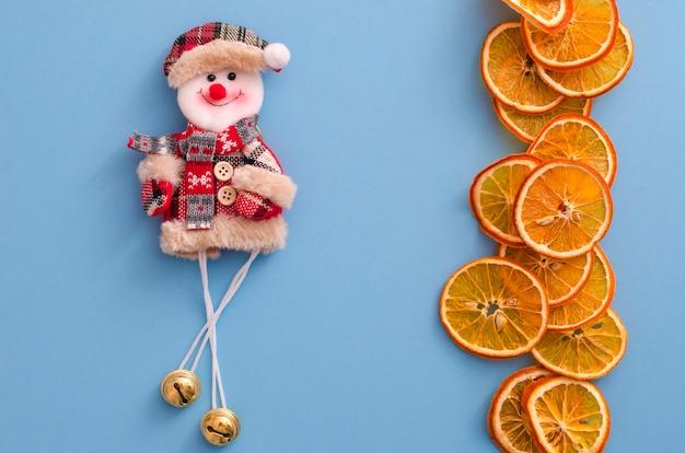 乾燥スライスオレンジ柑橘系の果物と明るい青の背景に面白い雪だるま。