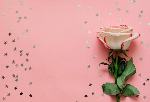テキストのための場所でピンクの背景にホログラフィック星とバラの花