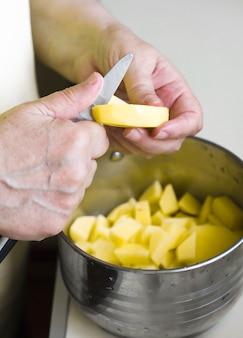 おばあちゃん、ジャガイモを金属製のパンにナイフで切る