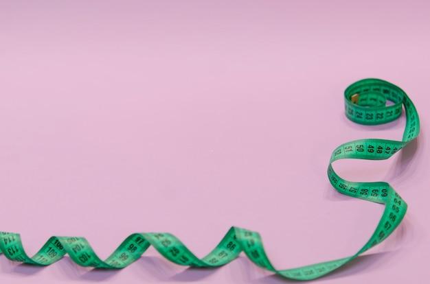 紫色の背景に螺旋状にひねられた緑色の測定用テープ
