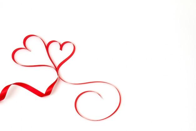 Соедините красное сердце ленты на белой предпосылке и скопируйте космос.