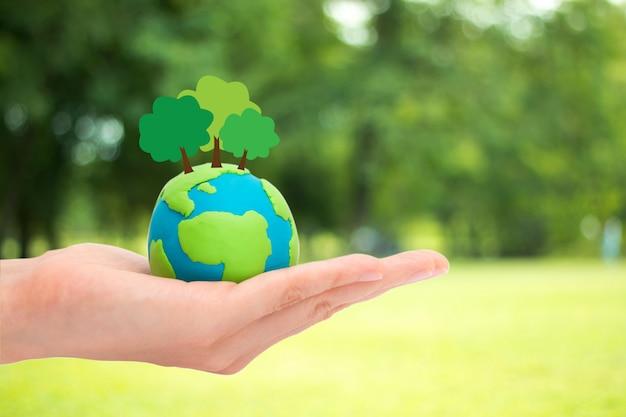 ぼやけている緑豊かな庭園の自然背景に地球、惑星または地球上の人間の手持ち株植物の木。生態学のコンセプトです。