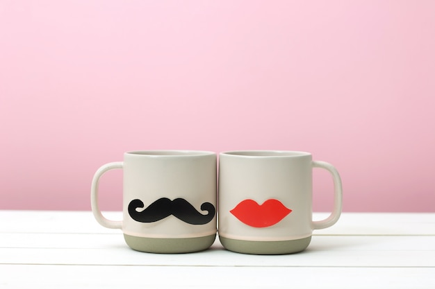 紙のハートの形の偽の唇と白の木製テーブルピンク背景上のピンクのカップの口ひげの装飾。