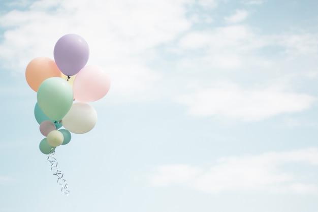 水色の空にカラフルな柔らかいパステル風船のグループ。