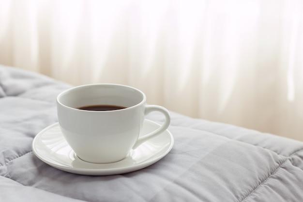 朝のベッドの背景にコーヒーカップ