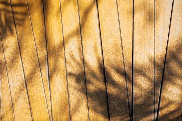 Абстрактная предпосылка листьев ладони теней на деревянной стене.