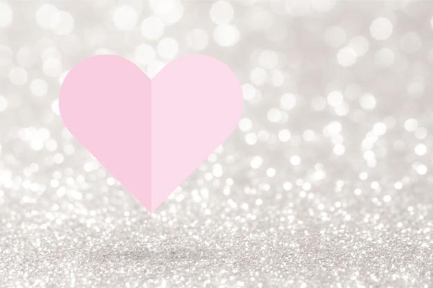 ピンクのハート紙はあなたのテキストのコピースペースと銀のキラキラ背景に折ります。