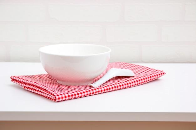 空の白いボウルとレンガの壁紙の背景を持つテーブルの上の赤いテーブルクロスの上のスプーン